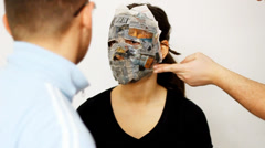 Make a mask with newspaper clippings Stock Footage