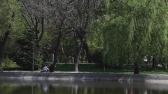 Lake, people walking in the park, city, beautiful spring day Stock Footage