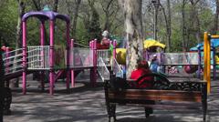 Happy kids running on children's playground, beautiful spring day - stock footage