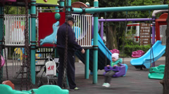 Grandfather and grandson on a playground, kid, child, swing, slide, spring Stock Footage