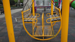 Big empty yellow swing on children's playground Stock Footage