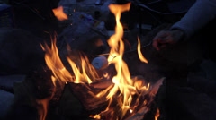 A camper roasts a marshmallow over a camp fire - stock footage
