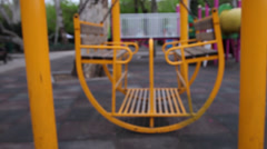Blurred big empty yellow swing on children's playground, out of focus Stock Footage