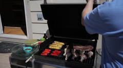 Backyard Barbeque man opens grill with chicken, corn, steak - 3 clips - stock footage