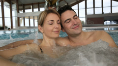 Couple relaxing in hot water tub of spa center Stock Footage