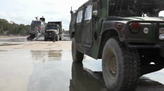 Humvee parked in foreground of truck backing onto hovercraft ramp  (HD) Stock Footage