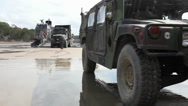 Stock Video Footage of humvee parked in foreground of truck backing onto hovercraft ramp  (HD)