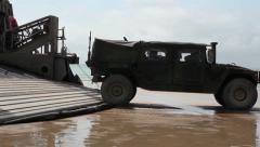 Humvee backs onto hover craft on sandy beach  (HD) Stock Footage