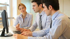 Business people meeting in front of desktop Stock Footage