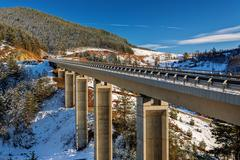 mountain bridge in winter with snow and blue sky - stock photo