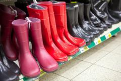 Diferent red and black waterboots are on the shop shelves Stock Photos