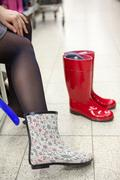 dressing and buying rainboots in shoeshop - stock photo