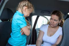 Resentful child refusing get in safety seat under mother severe look Stock Photos