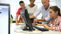 Teacher with students in computing class Stock Footage