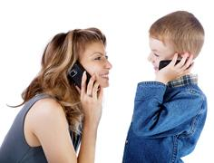 Girl and  boy talk by a cellular telephone Stock Photos