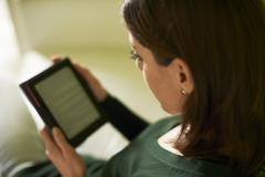 Girl studying literature with e-book at home Stock Photos