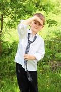 the little boy unties a tie against green - stock photo