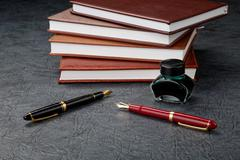 fountain pens with ink and a pile of organizers - stock photo
