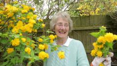 Portrait of senior woman gardener with yellow flowers, steadicam shot Stock Footage
