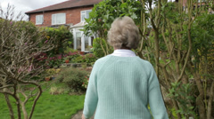 Senior woman walks up garden path, steadicam shot Stock Footage