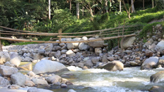 Mountain river rapids and bamboo bridge . Dumaguete, Philippines. - stock footage