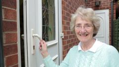 Senior woman opens back door of house and smiles, steadicam shot Stock Footage