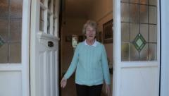 Senior woman opens front door and welcomes visitor, steadicam shot Stock Footage