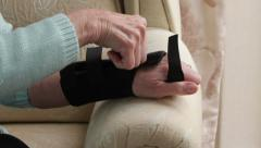 Senior woman puts on wrist brace at home Stock Footage