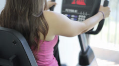 Woman exercising on a stationary bike in a gym Stock Footage