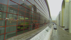 Car rides near glass wall of Mosekspo pavilion at winter Stock Footage