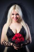 black widow in grief  with flowers  with a veil - stock photo