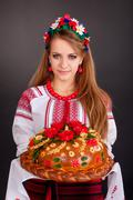 Young woman in ukrainian clothes, with garland and round loaf Stock Photos