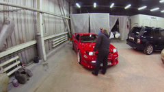 Man opens bonnet of red sport car and other one comes closer Stock Footage