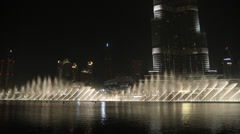 Fountain near Burj Khalifa illuminated by the city at night, - stock footage
