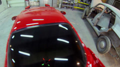 Man drives red sport car which moves backward in service garage Stock Footage