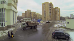 People walk by street with cars ride near truck and loader Stock Footage