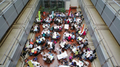 Young people are discussing at the tables located on first floor Stock Footage