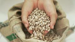 Beans Falling Through Fingers into Bag - stock footage