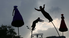 Silhouettes of aerialists swinging on five-meter poles Stock Footage