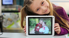 Little girl scrolls the family photos on a tablet PC Stock Footage
