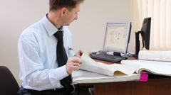 Man sitting in the office and looking wallpaper sample Stock Footage