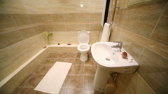 Modern toilet room with brown tiles on floor and walls Stock Footage