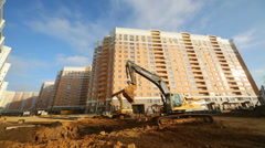 Excavator digs ground near high multi-storey building Stock Footage