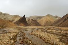 Lifeless orange rocks and a river during the sand storm, iceland Stock Photos