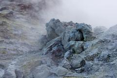 White toxic steam raising behind big colored rock in iceland Stock Photos