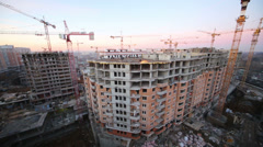 Builders working on a large building construction at a sunset Stock Footage