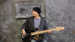 Young man in striped vest and knitted jacket sits with guitar Stock Footage