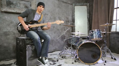 Young musician plays bass electric guitar sitting on amplifier Stock Footage