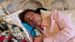 Young man in pink shirt sleeps on bed at the studio Stock Footage