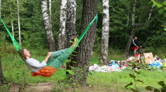 Young girl lies in hammock on nature near the pile of garbage Stock Footage